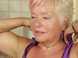 Blonde mature slut doing herself in the kitchen